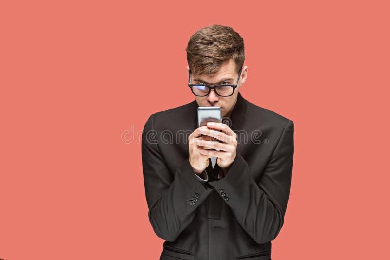 El hombre de negocios caucásico joven en fondo rojo que habla en el teléfono celular foto de archivo