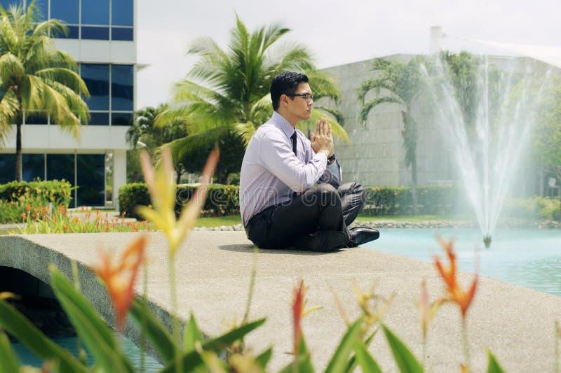 El hombre de negocios chino medita yoga fuera del edificio de oficinas fotografía de archivo