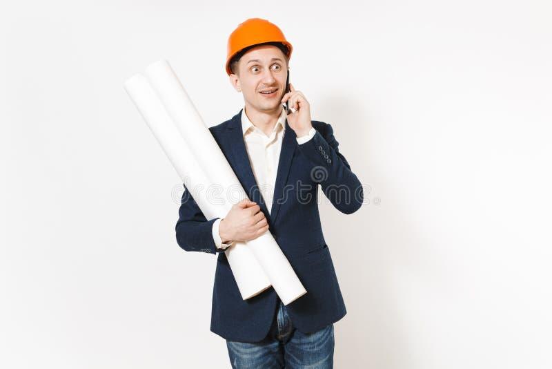 El hombre de negocios chocado joven en traje oscuro, casco de protección protector celebra planes de los modelos, negociaciones s imagenes de archivo
