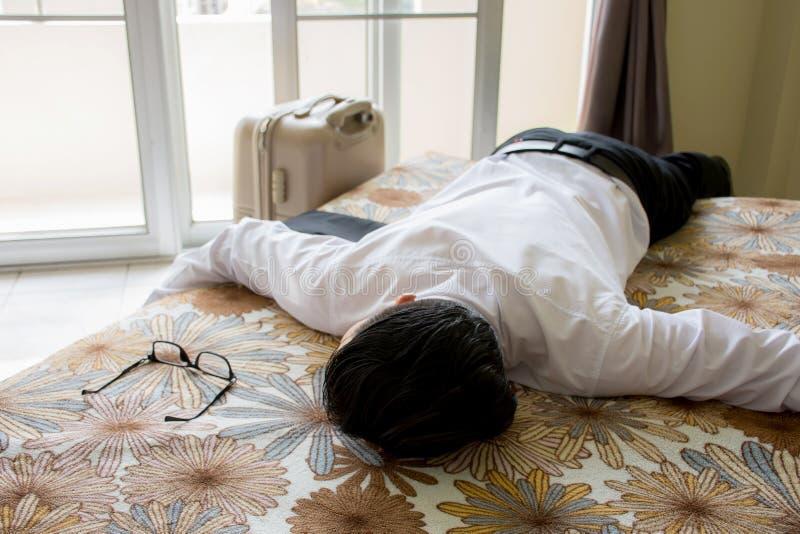 El hombre de negocios coloca en cama y consigue dormir con equipaje y vidrios después de probado de viaje imagen de archivo libre de regalías