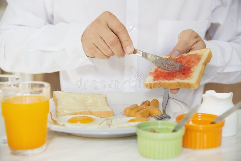 El hombre de negocios come el desayuno americano imagen de archivo libre de regalías