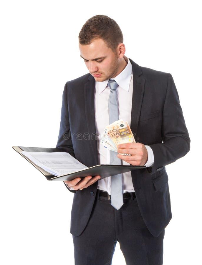 El hombre de negocios con el dinero está leyendo algunos papeles imagen de archivo