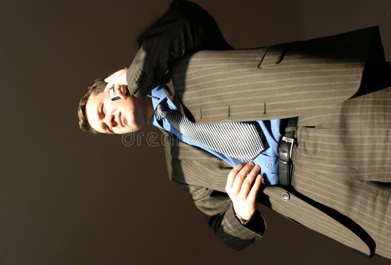 El hombre de negocios con el teléfono móvil está mirando fijamente en el sol imagen de archivo libre de regalías