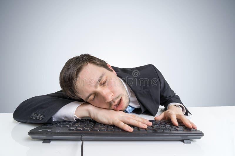 El hombre de negocios con exceso de trabajo cansado o agotado está durmiendo en el teclado imagen de archivo