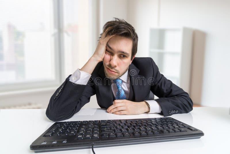 El hombre de negocios con exceso de trabajo y cansado está trabajando con el ordenador en oficina imagen de archivo
