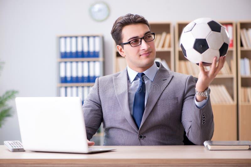 El hombre de negocios con la bola del fútbol en oficina imagen de archivo