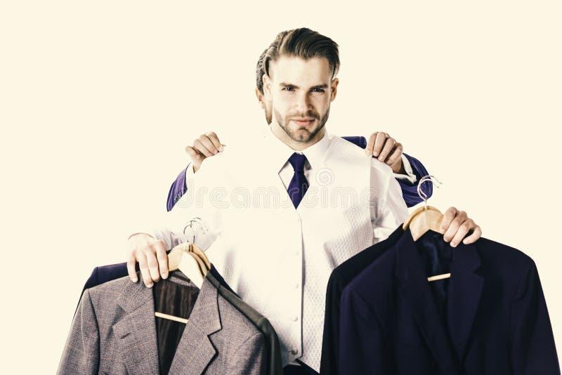 El hombre de negocios con la cara seria compra chaquetas de lujo El hombre de negocios elige el equipo con las manos del ayudante fotos de archivo