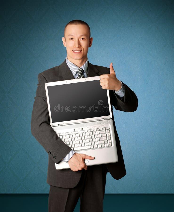 El hombre de negocios con la computadora portátil abierta muestra welldone fotografía de archivo