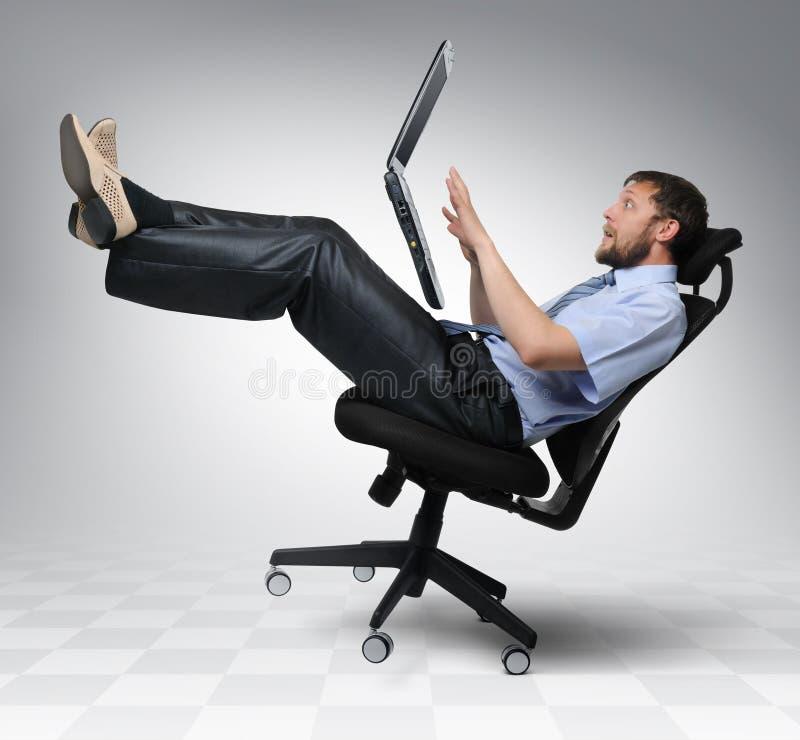 El hombre de negocios con la computadora portátil se cae de una silla imagenes de archivo