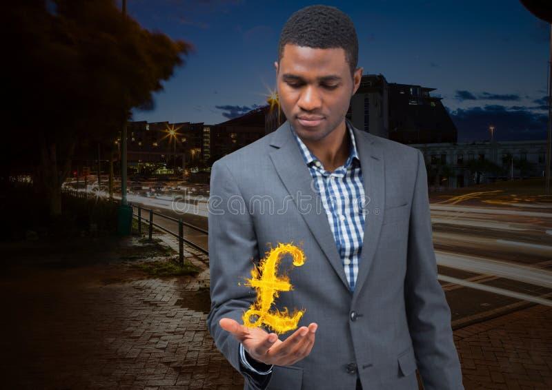 el hombre de negocios con la extensión de la mano con de libras enciende el icono encima en la ciudad en la noche imágenes de archivo libres de regalías
