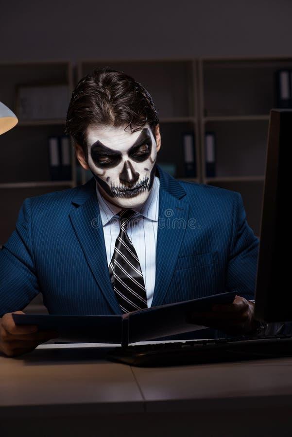 El hombre de negocios con la mascarilla asustadiza que trabaja tarde en oficina imagenes de archivo