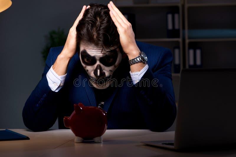 El hombre de negocios con la mascarilla asustadiza que trabaja tarde en oficina fotografía de archivo