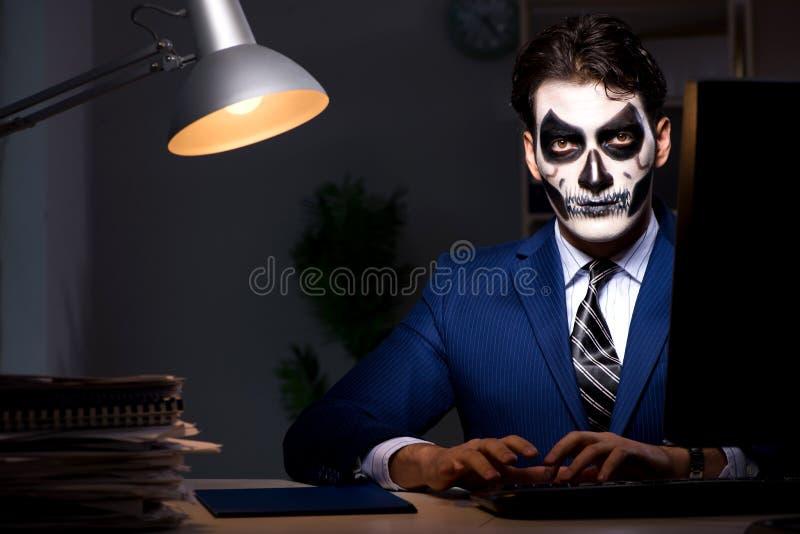 El hombre de negocios con la mascarilla asustadiza que trabaja tarde en oficina imagen de archivo