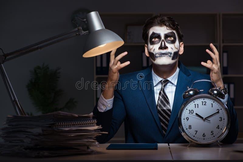 El hombre de negocios con la mascarilla asustadiza que trabaja tarde en oficina foto de archivo