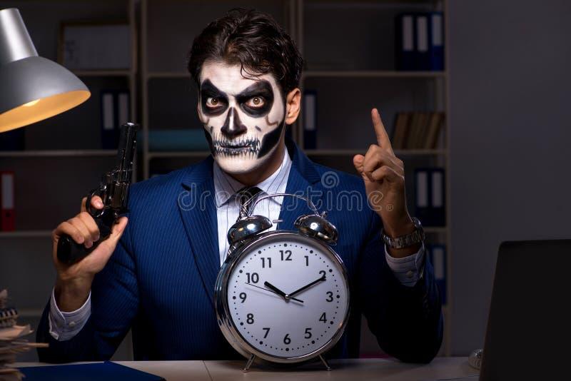 El hombre de negocios con la mascarilla asustadiza que trabaja tarde en oficina foto de archivo libre de regalías