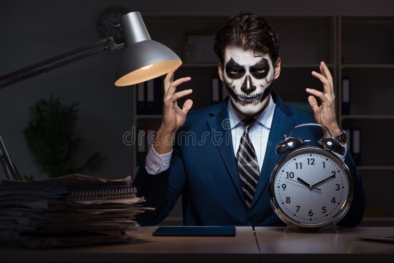 El hombre de negocios con la mascarilla asustadiza que trabaja tarde en oficina fotos de archivo