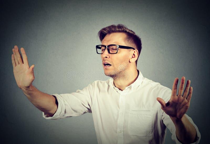 El hombre de negocios con los ojos vendados que estira los brazos hacia fuera observa ciego cerrado foto de archivo