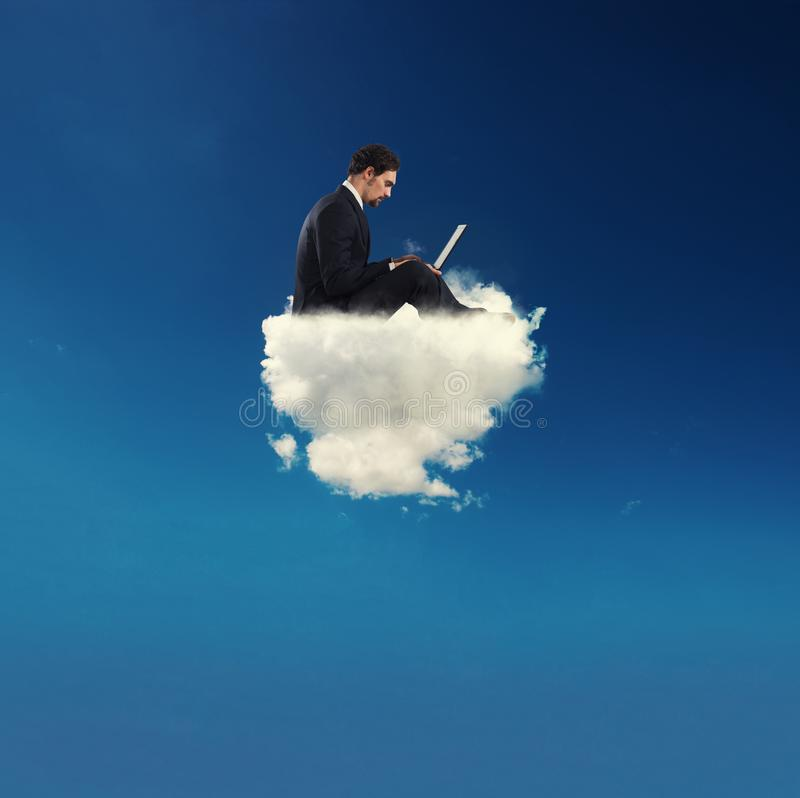 El hombre de negocios conectó con su ordenador portátil sobre una nube concepto de apego social de la red y de Internet fotos de archivo libres de regalías