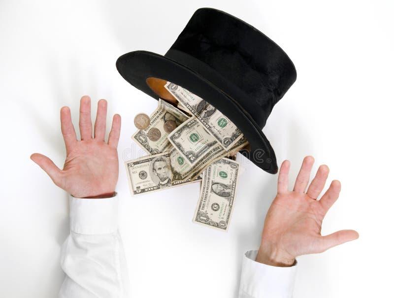 El hombre de negocios conjura muchos dólares de un sombrero negro viejo imagen de archivo libre de regalías