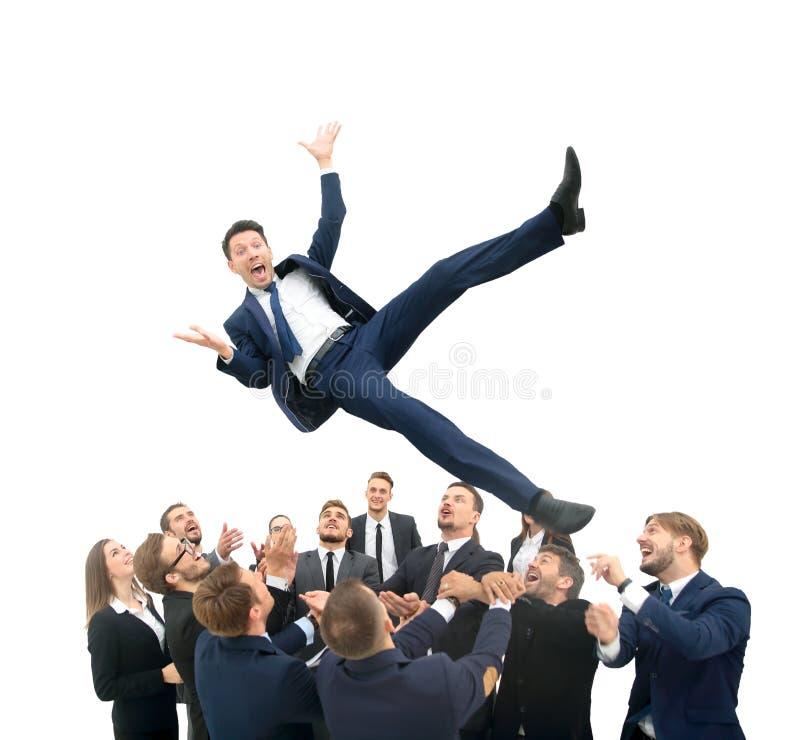 El hombre de negocios consigue lanzado en el aire por los trabajadores del co durante celebra foto de archivo libre de regalías