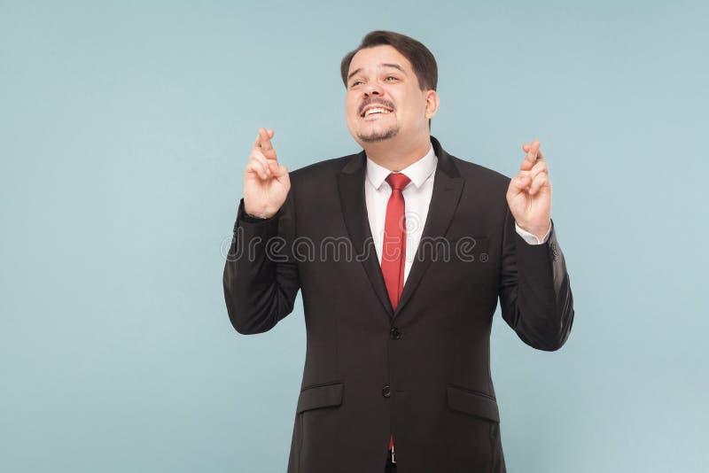 El hombre de negocios cruza sus fingeres y esperanzas de la suerte imagen de archivo