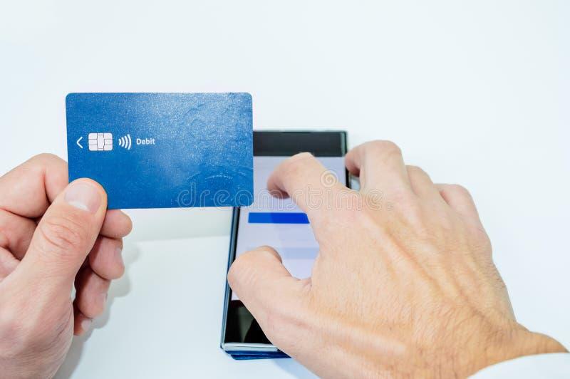 El hombre de negocios da sostener una tarjeta de crédito y usar el smartphone para las compras en línea imagen de archivo