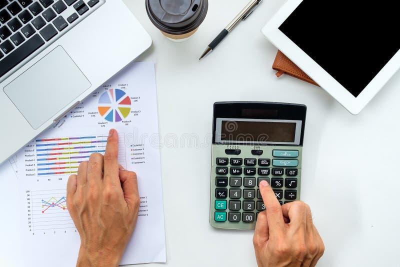 El hombre de negocios da el trabajo en la calculadora con informe financiero imágenes de archivo libres de regalías