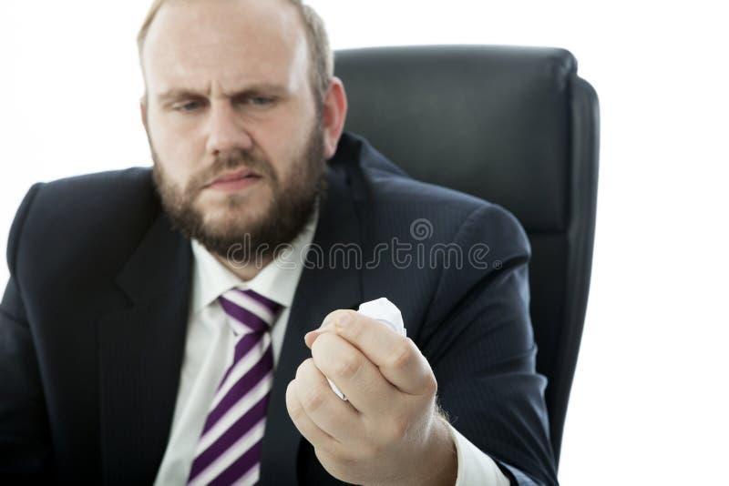 El hombre de negocios de la barba arruga la hoja del papel fotografía de archivo