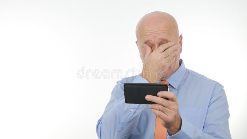 El hombre de negocios decepcionado Read Bad News en hace tabletas y hace gestos de mano nerviosos foto de archivo