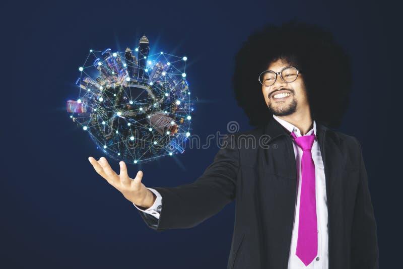 El hombre de negocios del Afro sostiene la ciudad con la red de la conexión imagenes de archivo