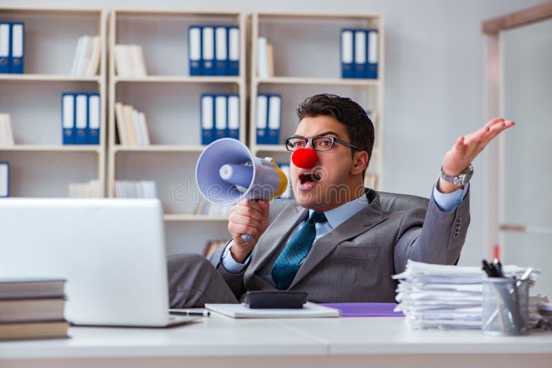 El hombre de negocios del payaso enojado en la oficina con un megáfono fotografía de archivo