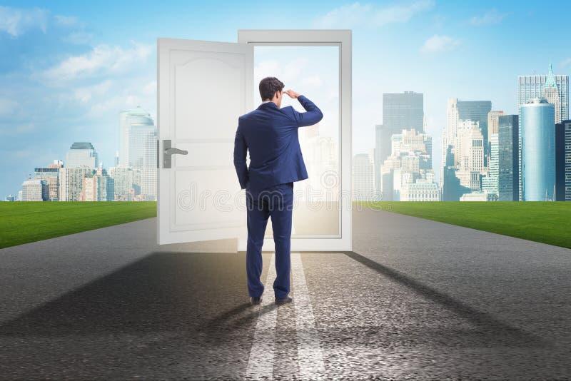El hombre de negocios delante de la puerta en concepto de las oportunidades de negocio fotografía de archivo