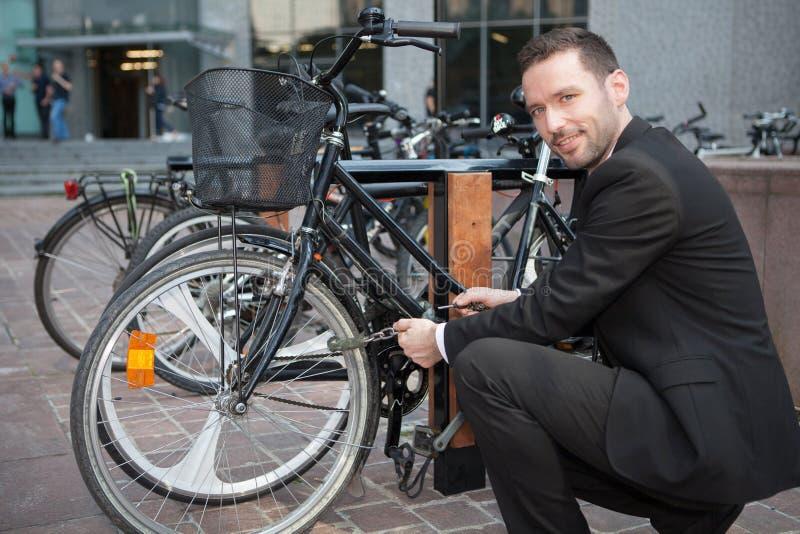 El hombre de negocios desbloquea su bici después de un día de trabajo foto de archivo