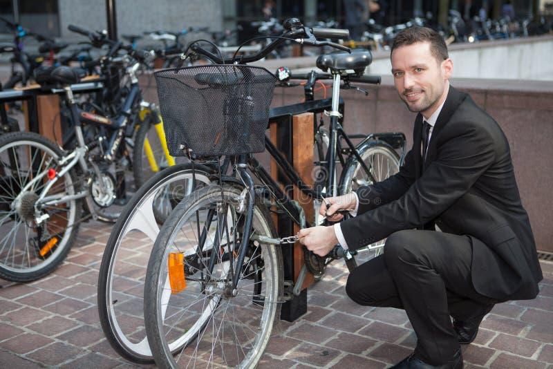El hombre de negocios desbloquea su bici después de un día de trabajo imagenes de archivo