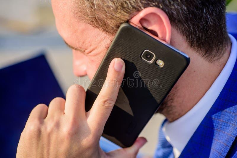 El hombre de negocios detiene smartphone cerca de cierre del oído Concepto de la consulta y de la ayuda Cómo puedo ayúdele Llamad foto de archivo