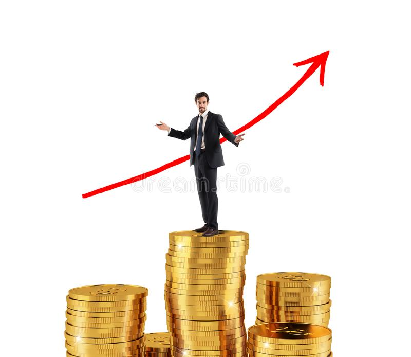 El hombre de negocios dibuja la flecha creciente de las estadísticas de la compañía sobre una pila de dinero imagen de archivo