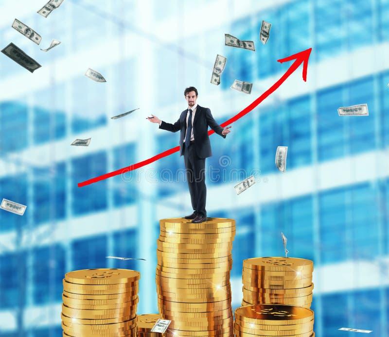 El hombre de negocios dibuja la flecha creciente de las estadísticas de la compañía sobre una pila de dinero imágenes de archivo libres de regalías