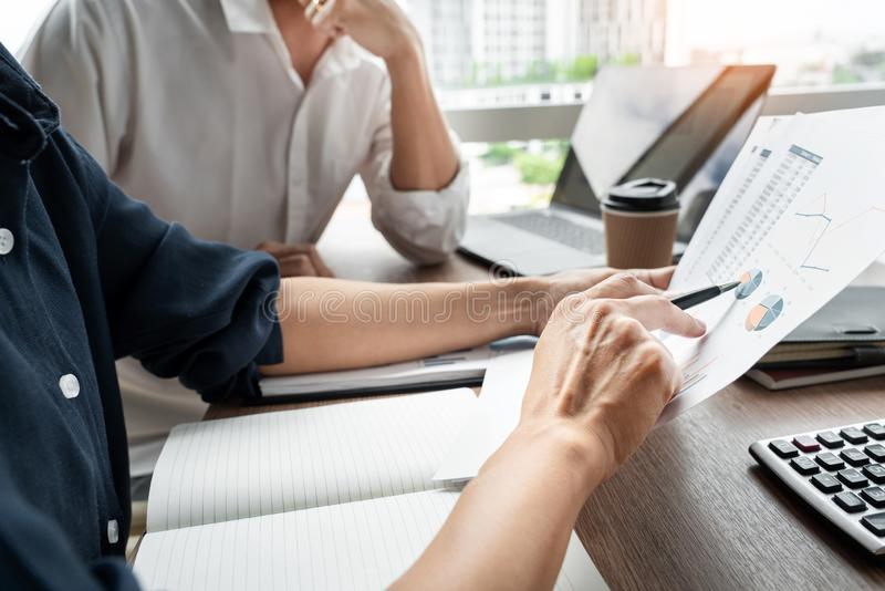 El hombre de negocios discute el explicar de la nueva información de las tendencias sobre un documento con el compañero de trabaj fotos de archivo libres de regalías