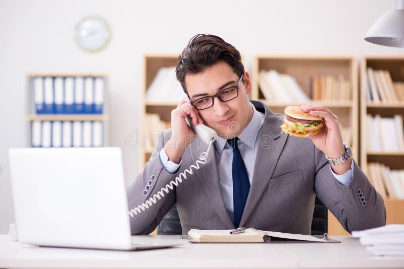 El hombre de negocios divertido hambriento que come el bocadillo de la comida basura fotografía de archivo libre de regalías