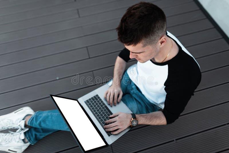 El hombre de negocios elegante joven en una camisa elegante en vaqueros se sienta en un piso de madera y trabaja en un ordenador  imagen de archivo libre de regalías