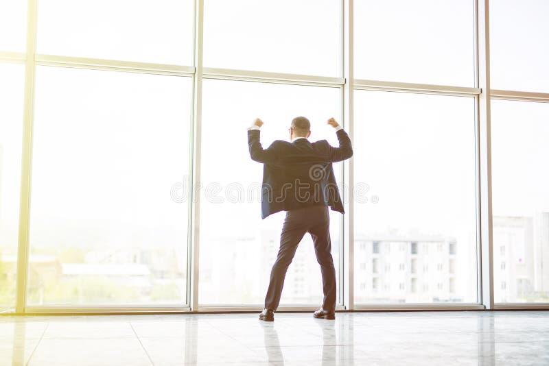 El hombre de negocios emocionado de la Edad Media con la victoria reised las manos para arriba delante de la ventana panorámica e fotos de archivo libres de regalías
