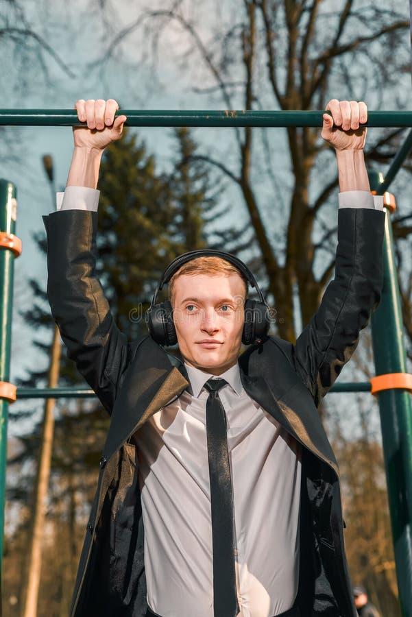El hombre de negocios en auriculares se tira para arriba en una barra horizontal de los deportes Hombre joven moderno Concepto de imagen de archivo libre de regalías