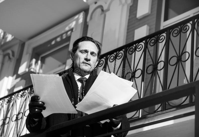 El hombre de negocios en capa examina seriamente los documentos, día, al aire libre fotos de archivo