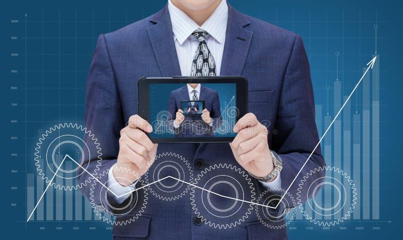 El hombre de negocios en crecimiento del fondo de la carta demuestra en el dispositivo móvil sí mismo foto de archivo