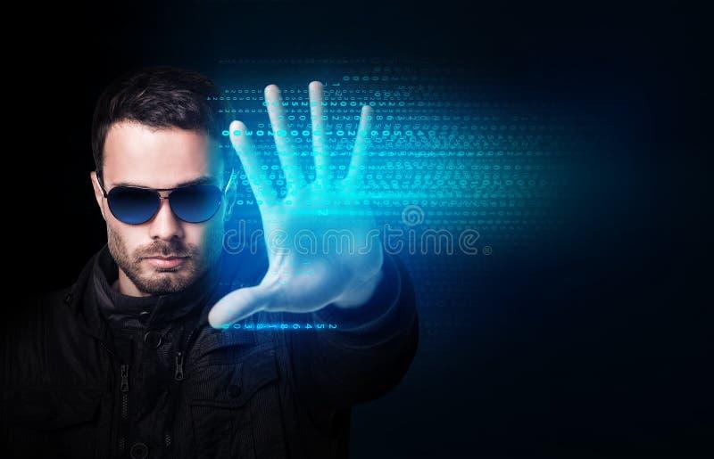 El hombre de negocios en gafas de sol controla código de ordenador que brilla intensamente virtual fotos de archivo