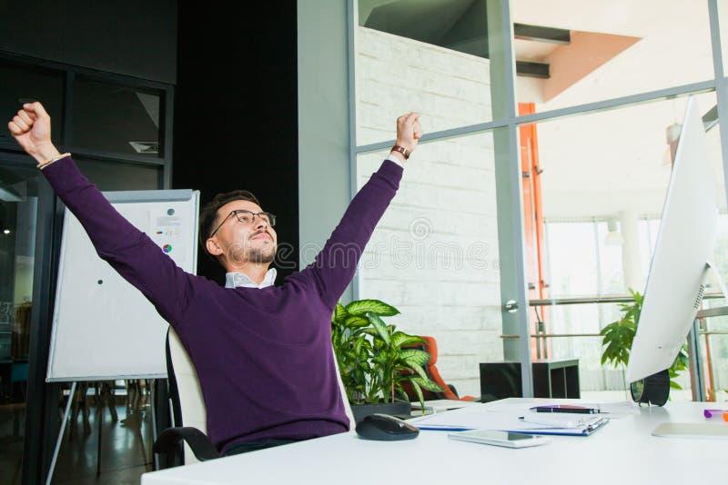 El hombre de negocios en la oficina, gesto del éxito, meta alcanzó, hombre feliz imagen de archivo libre de regalías
