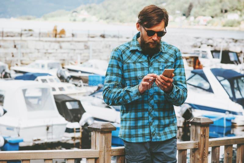 El hombre de negocios en las vacaciones alquila un yate por tecnología del éxito de la forma de vida del smartphone foto de archivo libre de regalías