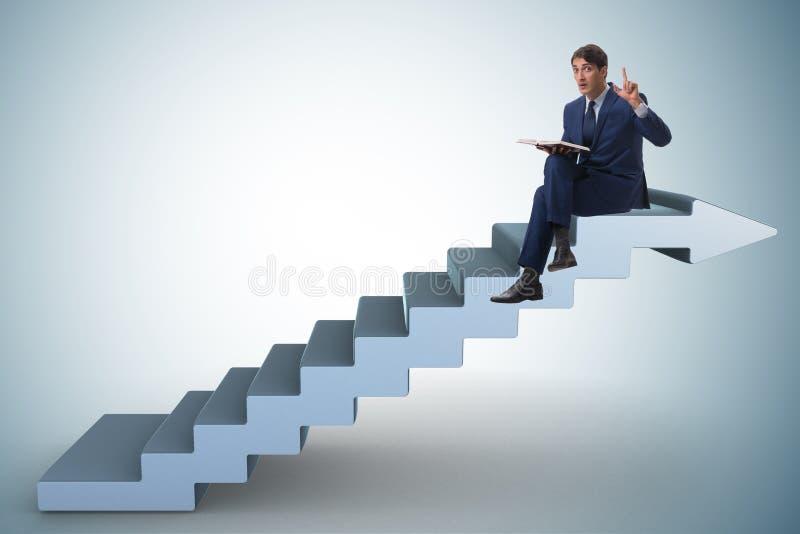 El hombre de negocios en libro de lectura del concepto de la escalera de la carrera fotografía de archivo libre de regalías