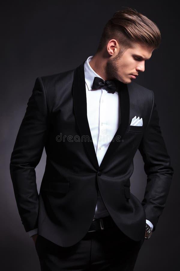 El hombre de negocios en negro con las manos en bolsillos mira lejos fotografía de archivo libre de regalías