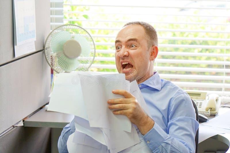 El hombre de negocios en su escritorio lanza documentos y los papeles en el aire fotografía de archivo